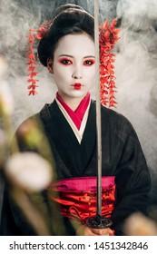 selective focus of beautiful geisha in black kimono holding katana in smoke and sakura branches