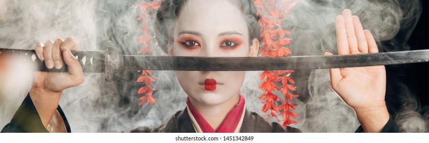 selective focus of beautiful geisha in black kimono holding katana in smoke, panoramic shot