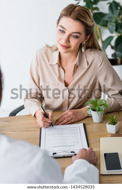 selective focus of beautiful patient signing document and looking at doctor