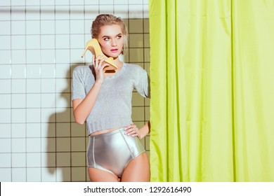 selective focus of beautiful young holding woman using heeled shoe as phone in shower