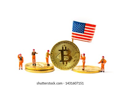 selective focus of bit coin and  miniature workers man with United State flag isolated on white background, creative image for money and saving concept.
