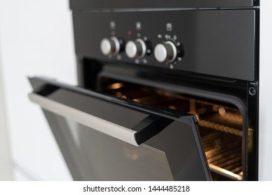Selective focus of black and modern built in oven with open glass door on white contemporary kitchen