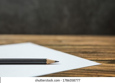 Selective focus of Black pencil on white paper on a wooden table and copy space
