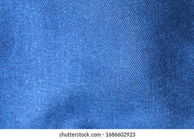 Selective focus blue jean denim top view close up shot to the detail of fabric. textile material and cotton patter tough and durable garment style. For background or wallpaper with copy space for text