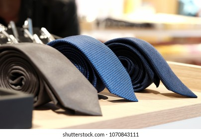 selective focus at blue necktie. Roll up necktie on the table and blur background . Concept of gentleman and necktie fashion, Shopping , father's day.