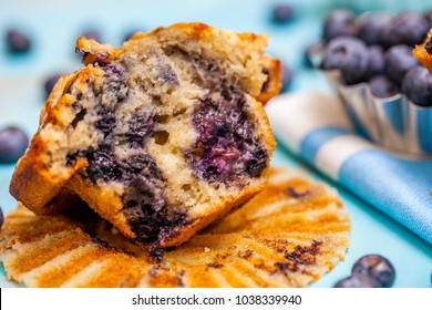 Selective focus of blueberry muffin half with bluberries in the background