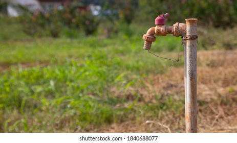 Selective focus with blurred background of grunge and rusty faucet installed in the field of remote rural area for people living and agriculture shows problem of water shortage and global warming.