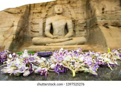 (Selective focus) Blurred Samadhi statue carved in stone in the background with beautiful flowers in the foreground. The Samadhi Statue is situated at Mahamevnawa Park in Anuradhapura, Sri Lanka.