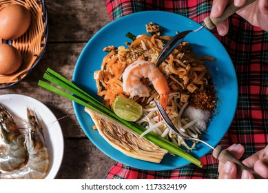 "Selective focus of boiled shrimp top on Stir fried noodles ""Pad Thai"" with young woman hand and many raw meat above on wooden table. Image for famous oriental cuisine with People and Food Concept"