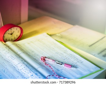 Selective focus of  book pen and clock on old desk