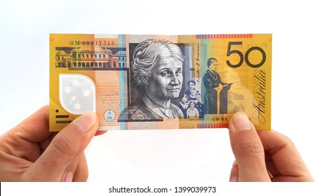 Selective focus of both hands holding the Australia fifty dollar bank note (50 AUD) with isolated white background.