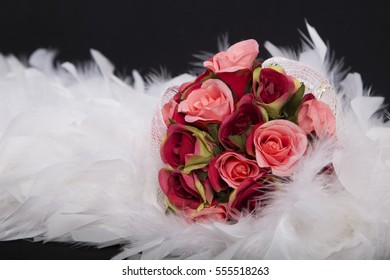 selective focus with a bouquet of red roses shade on white feather, beautiful Artificial flower sweet love on valentine or the anniversary day on black background, has copy space