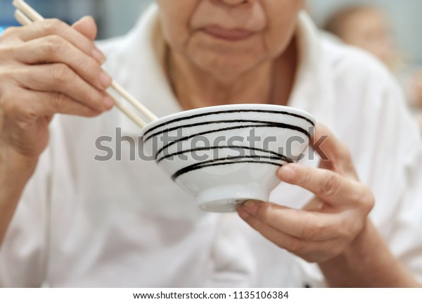 Selective focus at a bowl in elderly hand. Older Asia people holding a bowl and using chopsticks to eat food. Concept of culture of Asian eating food. healthcare and elderly people with good health.