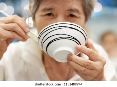 Selective focus at a bowl in old lady hand. Old Asia women holding a bowl and using chopsticks to eat food. Concept of culture of Asian eating food. healthcare and elderly people with good health.