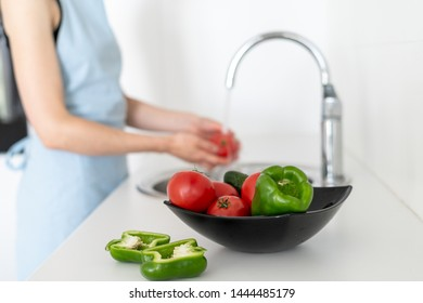 Selective focus of bowl with vegetables on blurred background with woman standing on white modern kitchen and washing tomato in sink
