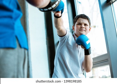 selective focus of boy in boxing gloves training with coach at gym