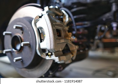 Selective focus of Brake Disc of the vehicle for repair.Automobile mechanic in process of new tire replacement.Car brake repairing in garage.Car Service and technician concept.