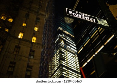 (selective focus) Broadway sign illuminated at night in Manhattan, New York. Blurred building on background.