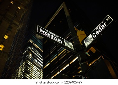 (selective focus) Broadway St. sign and Cedar St. sign illuminated at night in Manhattan, New York. Steam coming out of the manhole on the right side.