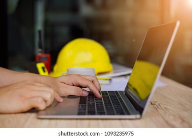 Selective focus. Bsiness man's hands typing on a laptop on a wooden desk in  site office.
