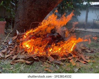 Selective focus of a burning fire, pollution from burning waste at open area, garbage from household, toxic burn trash danger, out of focus, noise and grain effects, enviroment concept.
