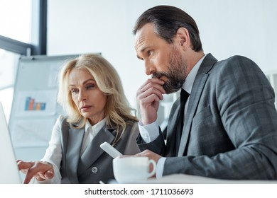 Selective focus of business woman working with laptop near pensive businessman with smartphone near coffee cup on table
