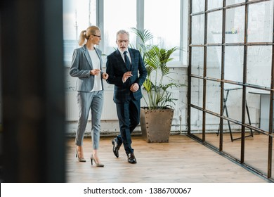 selective focus of businessman and businesswoman in eye glasses walking in office