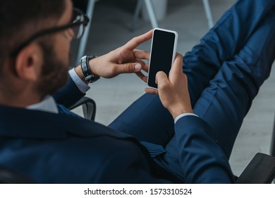 selective focus of businessman holding smartphone with blank screen