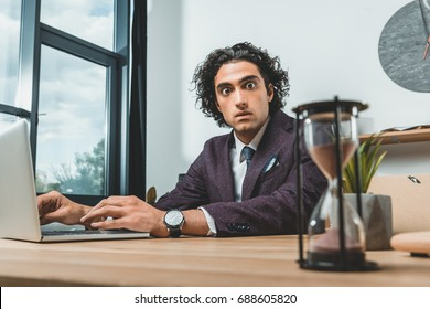 selective focus of businessman working on laptop and looking at sand clock while struggling to meet deadlines