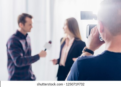 selective focus of businesswoman in suit giving interview to journalist at workspace