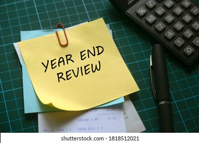 Selective focus of calculator,pen and a stack of memo notes written with Year End Review on a green square background.