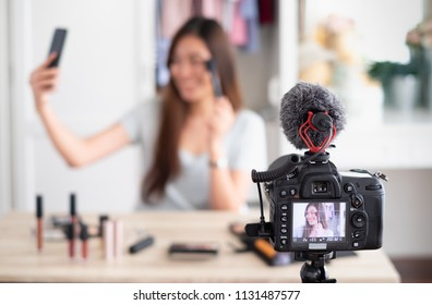 Selective focus at camera ,Asian blogger recording video and  selfie ford review cosmetic and make up  at home studio,influencer social media.