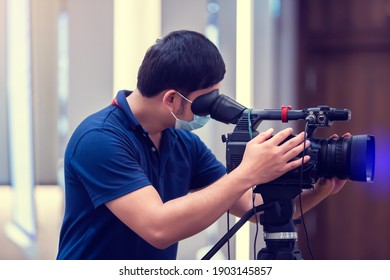 Selective focus to cameraman wearing mask with video camera set is recording in conference hall for seminar event. The concept of a photographer career with Covid-19 virus protection.