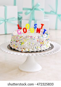 Selective focus of candles on a birthday cake on a cake stand with presents in the background