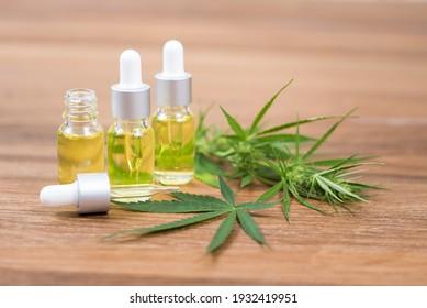 selektiver Fokus Cannabis-Ölextrakte in Tropfflaschen und Cannabisblätter auf Holzhintergrund