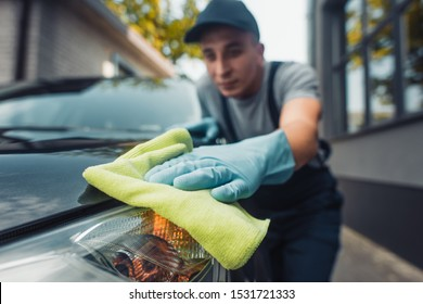 selective focus of car cleaner polishing headlamp with rag