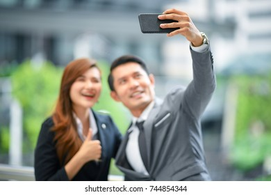 In selective focus at cell phone in hand. People alway social connecting.Happy businessman using mobile smartphone doing selfie with new partner. Digital World Business People Outdoor Meeting Concept.