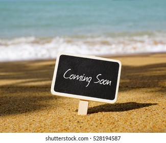 Selective focus of chalk board written with COMING SOON text. Wave and blue ocean background