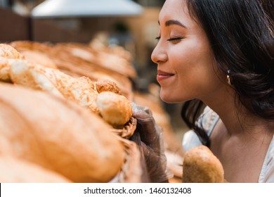 selective focus of cheerful asian woman smiling while smelling bread in supermarket