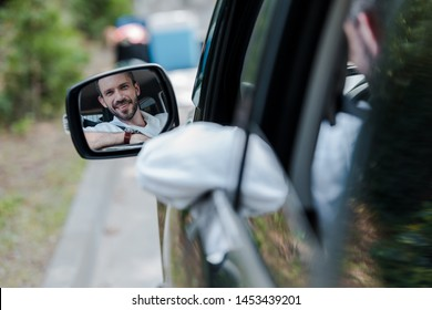selective focus of cheerful man looking at car window and smiling in car
