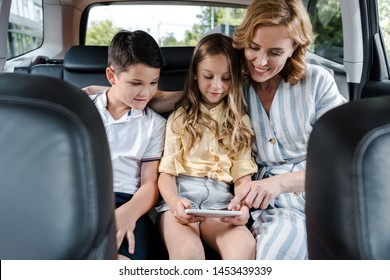 selective focus of cheerful mother pointing with finger at smartphone near kids in car