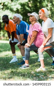 selective focus of cheerful senior and multicultural people doing stretching exercise on grass