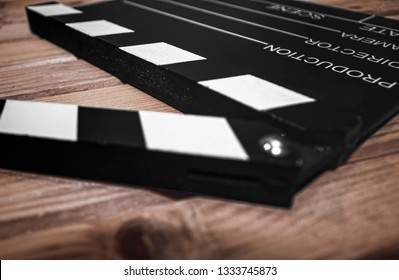 Selective focus of a Clapper board on a wood surface, cinema and videomaking concept