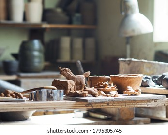 Selective focus of clay mold sculpture craft toys and pottery made by young girl. Kid activities concept. In process ceramic pieces placed on the wooden tray left to dry in sunlight.