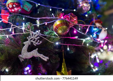 selective focus. close up of beautiful decorated christmas ball and doll on the tree with light at night. copy space for text. xmas or new year concept.