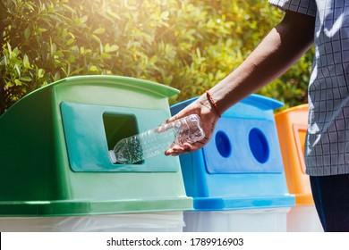 Selektiver Fokus, Nahaufnahme der schwarzen Hand, die eine leere Plastikflasche in den Müllabfall oder Abfalleimer wirft, Umweltrecyclingkonzept