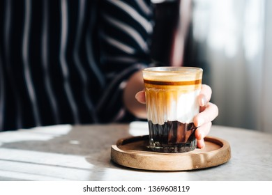 Selective focus and close up of Woman's hand hold a cup of mocha coffee on wooden plate and white table.