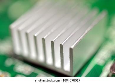 A selective focus closeup of an aluminum heatsink cooler on a green computer circuit board