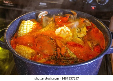 Selective focus closeup of a large blue pot filled with a traditional Cajun seafood boil of crab shrimp crawfish corn andouille sausage  in a spicy broth