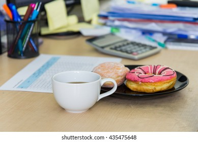 selective focus coffee cup and doughnut on office desk
